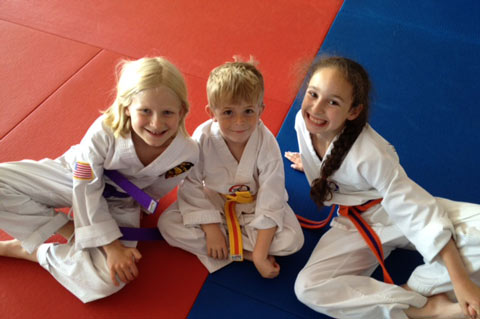 three kids smiling with martial arts uniforms